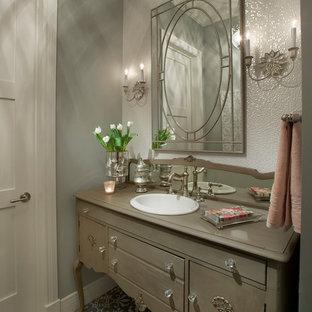 Пример оригинального дизайна: туалет в классическом стиле с фасадами островного типа, накладной раковиной, серыми стенами и коричневыми фасадами