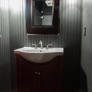 Стильный дизайн: маленький туалет в классическом стиле с открытыми фасадами, темными деревянными фасадами, серыми стенами, полом из ламината, консольной раковиной, столешницей из искусственного камня и коричневым полом - последний тренд