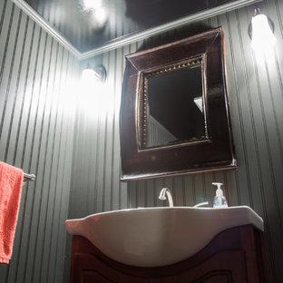 Пример оригинального дизайна: маленький туалет в классическом стиле с открытыми фасадами, темными деревянными фасадами, серыми стенами, полом из ламината, консольной раковиной, столешницей из искусственного камня и коричневым полом