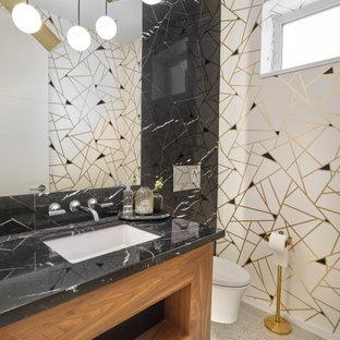 Пример оригинального дизайна: маленький туалет в современном стиле с плоскими фасадами, столешницей из искусственного кварца, фасадами цвета дерева среднего тона, разноцветными стенами, бетонным полом, врезной раковиной, серым полом и черной столешницей