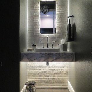 Inspiration pour un petit WC et toilettes design avec un sol marron, un mur gris, un placard sans porte, un carrelage gris, un carrelage en pâte de verre, un sol en bois foncé, une vasque et un plan de toilette en marbre.