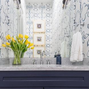 ヒューストンの中くらいのトランジショナルスタイルのおしゃれなトイレ・洗面所 (シェーカースタイル扉のキャビネット、青いキャビネット、マルチカラーの壁、アンダーカウンター洗面器、グレーの洗面カウンター、造り付け洗面台、壁紙) の写真