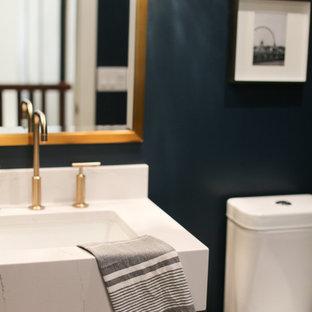 Idée de décoration pour un très grand WC et toilettes tradition avec un placard à porte plane, des portes de placard grises, un WC à poser, un mur bleu, un lavabo encastré, un plan de toilette en quartz modifié et un plan de toilette blanc.