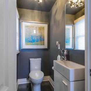 На фото: с невысоким бюджетом маленькие туалеты в стиле современная классика с плоскими фасадами, белыми фасадами, унитазом-моноблоком, серыми стенами, темным паркетным полом и раковиной с несколькими смесителями