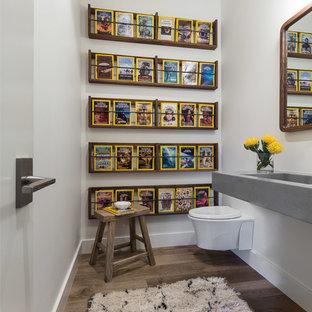 Пример оригинального дизайна: туалет в стиле рустика с белыми стенами, темным паркетным полом, монолитной раковиной, столешницей из бетона, серой столешницей и инсталляцией