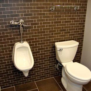 Aménagement d'un WC et toilettes industriel de taille moyenne avec un urinoir, un placard avec porte à panneau encastré, des portes de placard marrons, un mur gris, un sol en carrelage de porcelaine, un lavabo encastré, un plan de toilette en granite et un sol marron.