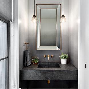 Modelo de aseo clásico renovado, pequeño, con paredes grises, lavabo integrado, encimera de cemento, suelo marrón, suelo de madera oscura y encimeras grises