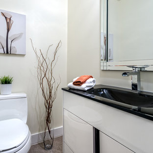 Inspiration for a small contemporary cloakroom in Montreal with flat-panel cabinets, white cabinets, a two-piece toilet, multi-coloured tiles, porcelain tiles, beige walls, porcelain flooring, engineered stone worktops, an integrated sink and black worktops.