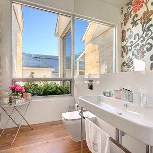 Idée de décoration pour un WC et toilettes design de taille moyenne avec un WC à poser, un carrelage rose, un carrelage blanc, carrelage en mosaïque, un mur multicolore, un sol en bois brun, un sol marron et un lavabo suspendu.