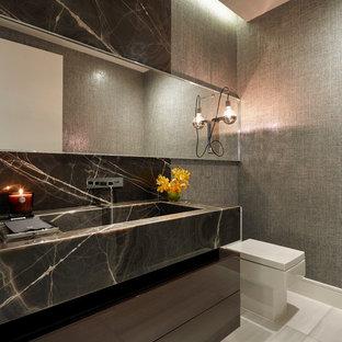 Foto de aseo contemporáneo, de tamaño medio, con sanitario de una pieza, encimera de mármol, armarios con paneles lisos, puertas de armario marrones, paredes grises y lavabo integrado