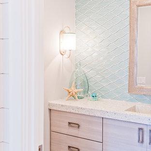 Réalisation d'un WC et toilettes marin de taille moyenne avec un placard à porte plane, des portes de placard en bois clair, un carrelage bleu, un carrelage en pâte de verre, un lavabo intégré et un plan de toilette en terrazzo.