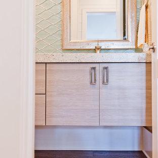 На фото: туалет среднего размера в морском стиле с плоскими фасадами, светлыми деревянными фасадами, синей плиткой, стеклянной плиткой, монолитной раковиной и столешницей терраццо