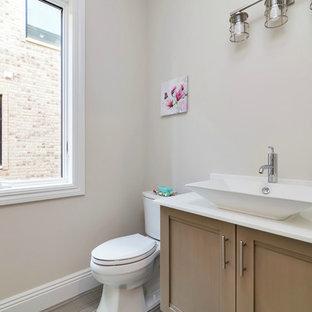 Пример оригинального дизайна: маленький туалет в стиле современная классика с фасадами с утопленной филенкой, бежевыми фасадами, раздельным унитазом, бежевыми стенами, полом из керамогранита, настольной раковиной, столешницей из искусственного камня и коричневым полом