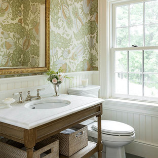 Design ideas for a traditional cloakroom in New York with freestanding cabinets, a two-piece toilet, multi-coloured walls, a submerged sink, grey floors, medium wood cabinets, slate flooring, marble worktops and white worktops.