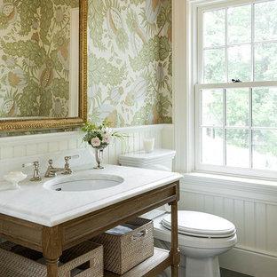Diseño de aseo clásico con armarios tipo mueble, sanitario de dos piezas, paredes multicolor, lavabo bajoencimera, suelo gris, puertas de armario de madera oscura, suelo de pizarra, encimera de mármol y encimeras blancas