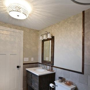 ワシントンD.C.の中サイズのラスティックスタイルのおしゃれなトイレ・洗面所 (家具調キャビネット、ヴィンテージ仕上げキャビネット、一体型トイレ、グレーのタイル、磁器タイル、ベージュの壁、無垢フローリング、アンダーカウンター洗面器、クオーツストーンの洗面台、白い床、白い洗面カウンター) の写真