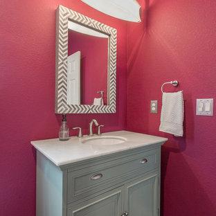 Esempio di un piccolo bagno di servizio classico con ante con bugna sagomata, ante blu, WC monopezzo, pareti rosa, parquet scuro, lavabo sottopiano, top in marmo e pavimento marrone