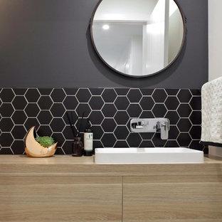 Идея дизайна: туалет в стиле модернизм с светлыми деревянными фасадами, инсталляцией, черной плиткой, плиткой мозаикой, черными стенами, столешницей из ламината и накладной раковиной