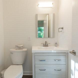 Ispirazione per un piccolo bagno di servizio con ante grigie, WC a due pezzi, pareti bianche, pavimento in cemento, lavabo integrato, top in superficie solida, pavimento grigio e top bianco