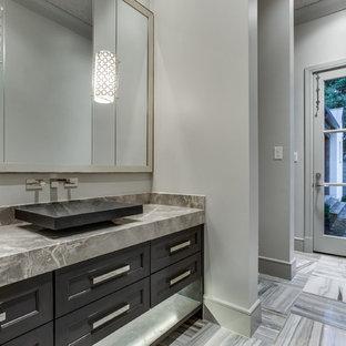 Immagine di un grande bagno di servizio tradizionale con WC monopezzo, piastrelle grigie, piastrelle in pietra, pareti grigie, pavimento in marmo, lavabo a bacinella, top in marmo, ante con riquadro incassato e ante grigie