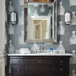 This is an example of a tropical powder room in Miami with furniture-like cabinets, dark wood cabinets, multi-coloured walls and white benchtops.