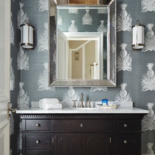 マイアミのトロピカルスタイルのおしゃれなトイレ・洗面所 (家具調キャビネット、濃色木目調キャビネット、マルチカラーの壁、白い洗面カウンター) の写真