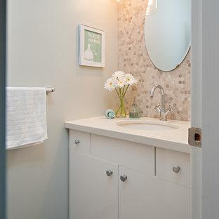Réalisation d'un petit WC et toilettes tradition avec un lavabo encastré, un placard à porte plane, des portes de placard blanches, un plan de toilette en quartz modifié, un mur gris, un sol en carrelage de porcelaine, des carreaux en allumettes et un plan de toilette blanc.