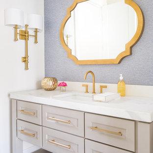 Idée de décoration pour un WC et toilettes tradition de taille moyenne avec un placard à porte shaker, des portes de placard beiges, un mur blanc, un lavabo encastré, un plan de toilette en marbre, un plan de toilette blanc et un sol gris.