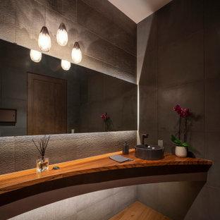 Réalisation d'un grand WC et toilettes design avec un placard sans porte, un carrelage gris, une vasque, un plan de toilette en bois, un sol marron, un plan de toilette marron et meuble-lavabo suspendu.