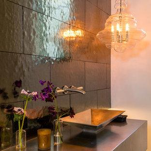 Foto di un bagno di servizio minimal con piastrelle grigie, piastrelle in gres porcellanato, pareti bianche, pavimento in legno massello medio, lavabo a bacinella, top in acciaio inossidabile e pavimento marrone