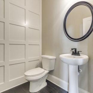 Aménagement d'un petit WC et toilettes classique avec un mur beige, un sol en bois foncé, un lavabo de ferme et un sol marron.