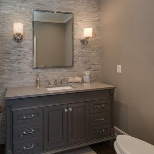 Idées déco pour un WC et toilettes classique de taille moyenne avec des portes de placard grises, un WC à poser, un carrelage gris, des carreaux en allumettes, un mur gris, un sol en bois foncé, un lavabo encastré, un plan de toilette en surface solide et un placard avec porte à panneau encastré.