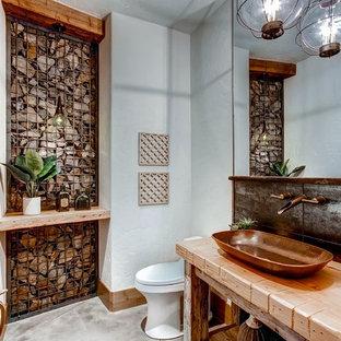 Cette image montre un WC et toilettes chalet avec un placard sans porte, un mur blanc, une vasque, un plan de toilette en bois, un sol gris et un plan de toilette marron.