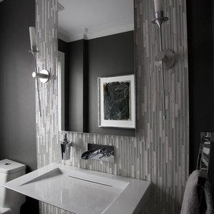 Imagen de aseo minimalista, grande, con sanitario de una pieza, baldosas y/o azulejos grises, paredes grises, suelo de madera oscura, lavabo suspendido y azulejos en listel