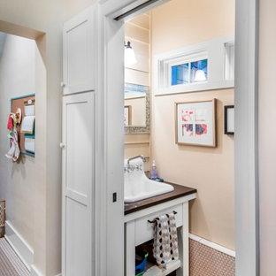Inspiration pour un petit WC et toilettes craftsman avec un lavabo posé, un placard en trompe-l'oeil, des portes de placard blanches, un plan de toilette en quartz modifié, un carrelage beige, des carreaux de céramique, un mur beige et un sol en carrelage de céramique.