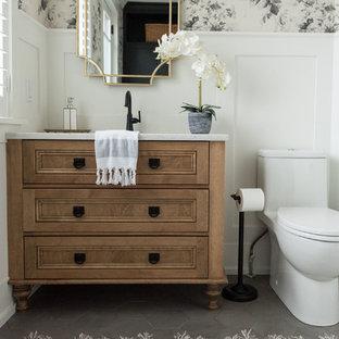 Cette image montre un WC et toilettes craftsman de taille moyenne avec un placard en trompe-l'oeil, des portes de placard en bois brun, un sol en carrelage de porcelaine, un lavabo encastré, un plan de toilette en quartz modifié, un sol gris et un plan de toilette blanc.