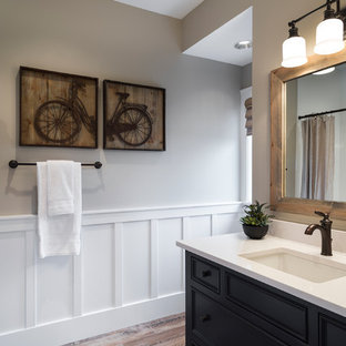 Inspiration for a transitional powder room remodel in Portland with an undermount sink, recessed-panel cabinets, black cabinets and white countertops