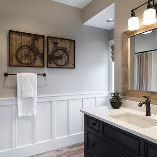 Ejemplo de aseo clásico renovado con lavabo bajoencimera, armarios con paneles empotrados, puertas de armario negras y encimeras blancas