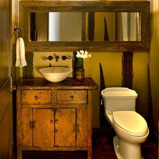 На фото: туалет среднего размера в стиле рустика с настольной раковиной, фасадами островного типа, оранжевыми фасадами, столешницей из дерева, раздельным унитазом, темным паркетным полом и коричневой столешницей с