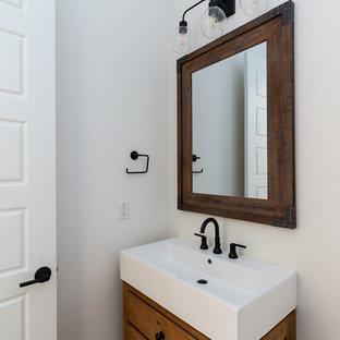 Стильный дизайн: туалет среднего размера в стиле кантри с фасадами островного типа, фасадами цвета дерева среднего тона, раздельным унитазом, белыми стенами, паркетным полом среднего тона, монолитной раковиной и коричневым полом - последний тренд