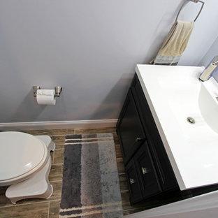 Cette photo montre un WC et toilettes chic de taille moyenne avec un placard à porte plane, des portes de placard grises, un mur gris, sol en stratifié et un sol marron.