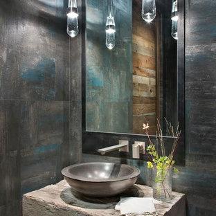 Modelo de aseo rústico, de tamaño medio, con paredes grises, lavabo sobreencimera y encimera de madera