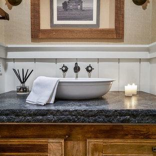 Aménagement d'un WC et toilettes campagne de taille moyenne avec un placard avec porte à panneau encastré, un mur beige, une vasque, un plan de toilette en granite, des portes de placard en bois brun et un plan de toilette gris.