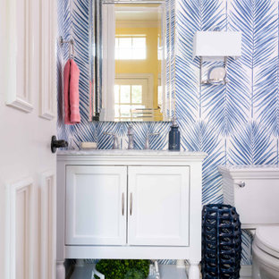 Inspiration for a small transitional dark wood floor and brown floor powder room remodel in Dallas with furniture-like cabinets, white cabinets, blue walls, white countertops and marble countertops