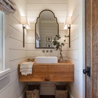 На фото: маленький туалет в стиле кантри с темным паркетным полом, настольной раковиной, коричневым полом, белыми стенами, столешницей из дерева и коричневой столешницей с