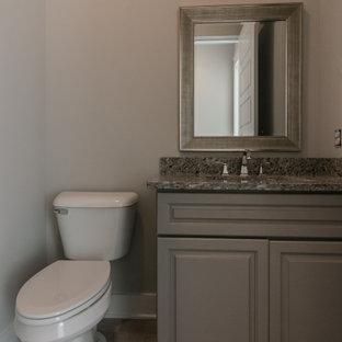 Kleine Country Gästetoilette mit profilierten Schrankfronten, grauen Schränken, Wandtoilette mit Spülkasten, grauer Wandfarbe, Vinylboden, Unterbauwaschbecken, Granit-Waschbecken/Waschtisch, braunem Boden und bunter Waschtischplatte in Nashville