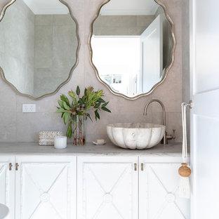 Ispirazione per un bagno di servizio tropicale di medie dimensioni con ante in stile shaker, ante bianche, WC sospeso, piastrelle beige, piastrelle in ceramica, pavimento con piastrelle in ceramica, lavabo a bacinella, top in granito, pavimento beige e top multicolore