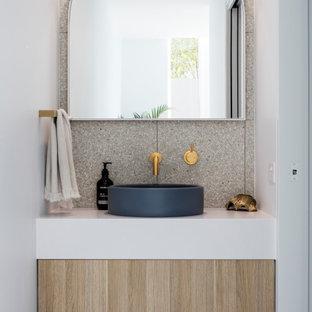 Inspiration pour un WC et toilettes marin avec un placard à porte plane, des portes de placard en bois clair, une vasque, un plan de toilette blanc et meuble-lavabo suspendu.