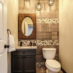 Cette image montre un petit WC et toilettes design avec un placard à porte shaker, des portes de placard noires, un WC séparé, un carrelage multicolore, des carreaux de porcelaine, un mur multicolore, un lavabo encastré, un plan de toilette en granite, un sol en carrelage de porcelaine et un sol beige.