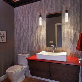 Immagine di un bagno di servizio contemporaneo con ante lisce, ante in legno scuro, WC monopezzo, piastrelle grigie, piastrelle in gres porcellanato, pareti grigie, pavimento in legno massello medio, top in quarzo composito e top rosso
